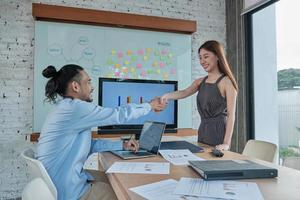 Businesspersons of Asian ethnicity are shaking hands to deal with commercial partnerships and work together after a beautiful young woman manager presents a success chart in the office meeting room. photo