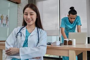 Portrait of beautiful female doctor of Asian ethnicity in uniform with stethoscope. Smile and looking at camera in a hospital clinic, male partner working behind her, two professional persons. photo