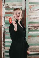 pretty blonde in black dress holding a stick of red candy photo