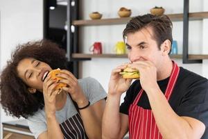 Pareja joven está alimentando mientras cocina una hamburguesa en la cocina foto