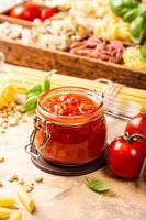 frasco de vidrio con pasta de tomate picante clásica casera o salsa de pizza. foto