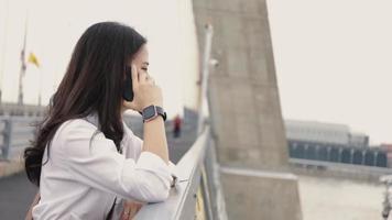mujer asiática hablando por teléfono afuera mientras está de pie en el puente. video