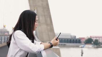 mujer asiática que usa el teléfono inteligente charlando con amigos y navegando por las redes sociales en un teléfono móvil mientras está de pie en el puente. video