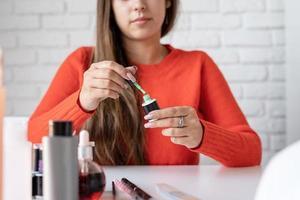 Hermosa influenciadora maestra de uñas caucásica con video chat o haciendo un blog foto