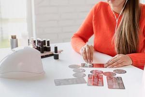 Nail master in bright clothes working at the nail salon photo