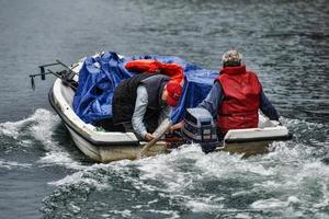 Lugo,Galicia, Spain,2021-Transporting boxes of grapes down the river in a motorboat from the vineyard to the tractor photo
