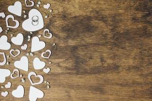 overhead view silver wedding rings heart shape wooden backdrop photo