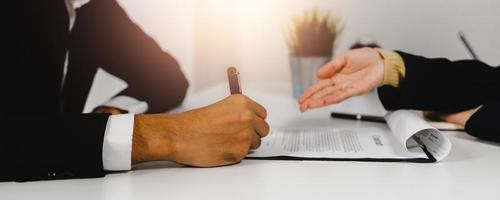 Cerrar signo de mano, explicación de la agencia bancaria y contrato de firma del empleado foto