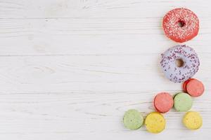 overhead view macaroons donuts wooden texture background photo