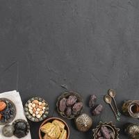 overhead view dates nuts baklava metallic plates black concrete textured backdrop with copy space photo