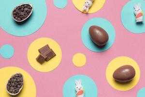 overhead view easter eggs rabbit choco chips round frame pink background photo