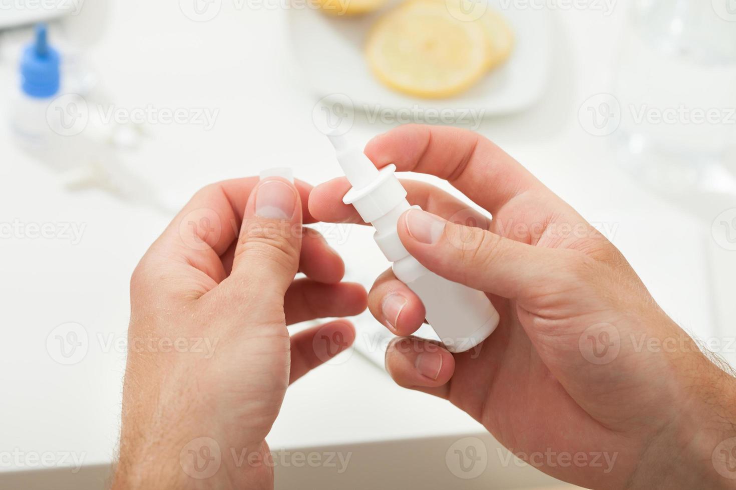 mani che tengono la bottiglia di goccia nasale foto