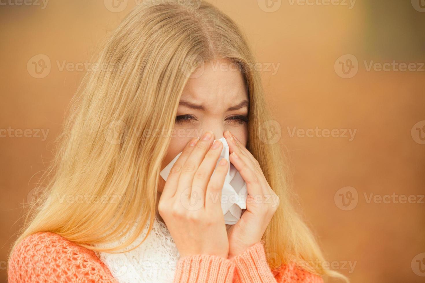 donna malata malata nel parco di autunno che starnutisce nel tessuto. foto