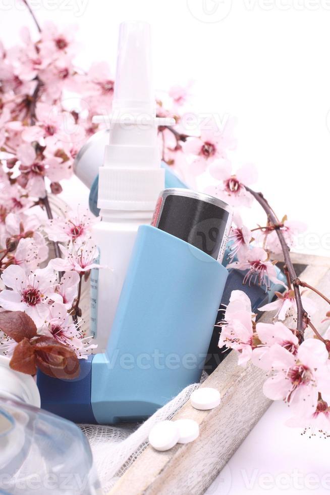 inalatori per l'asma con rami di alberi in fiore sul vassoio di legno foto