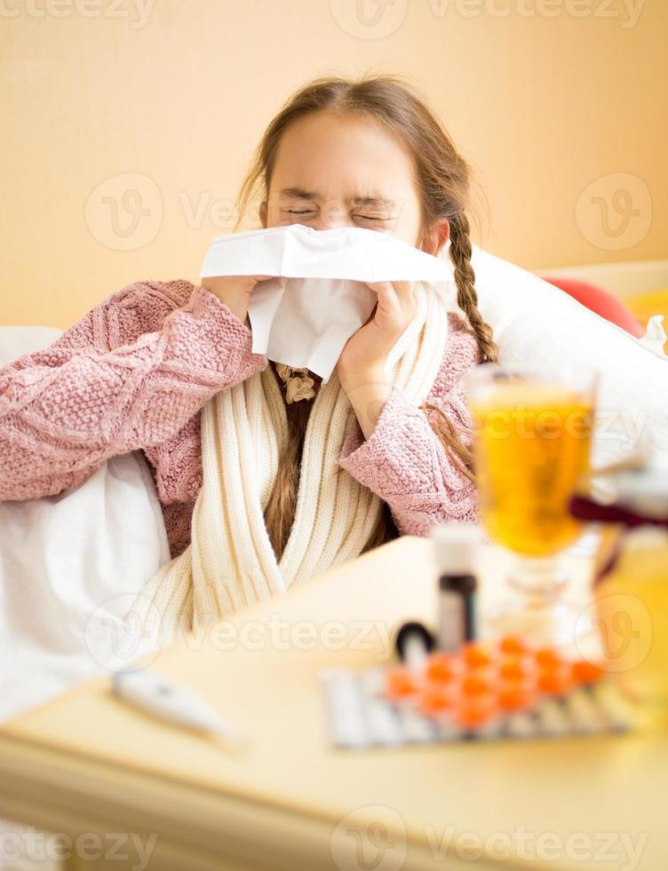 ragazza bruna sdraiata a letto e soffiando il naso nel tessuto foto