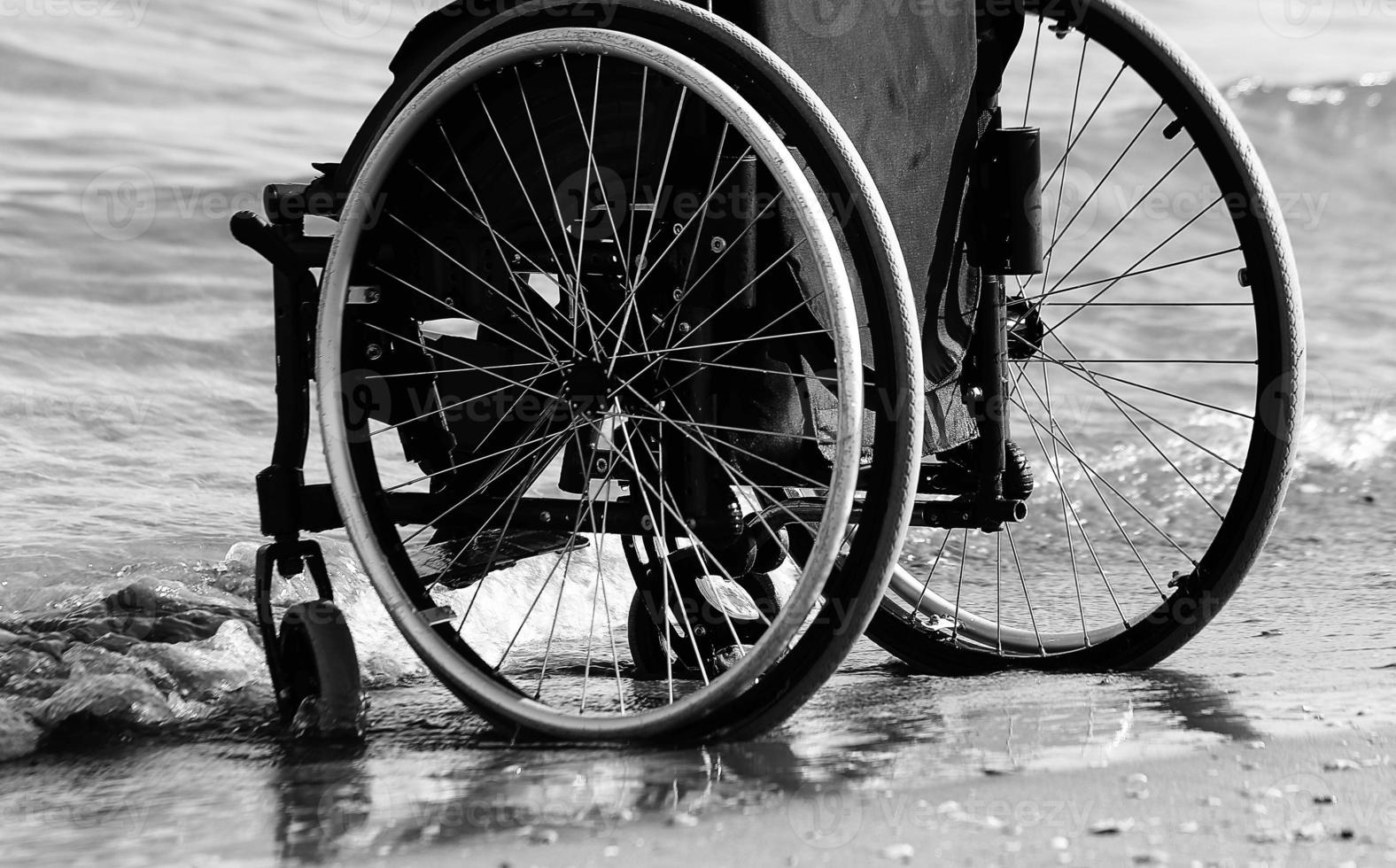 sedia a rotelle vicino al mare sulla spiaggia di sabbia foto