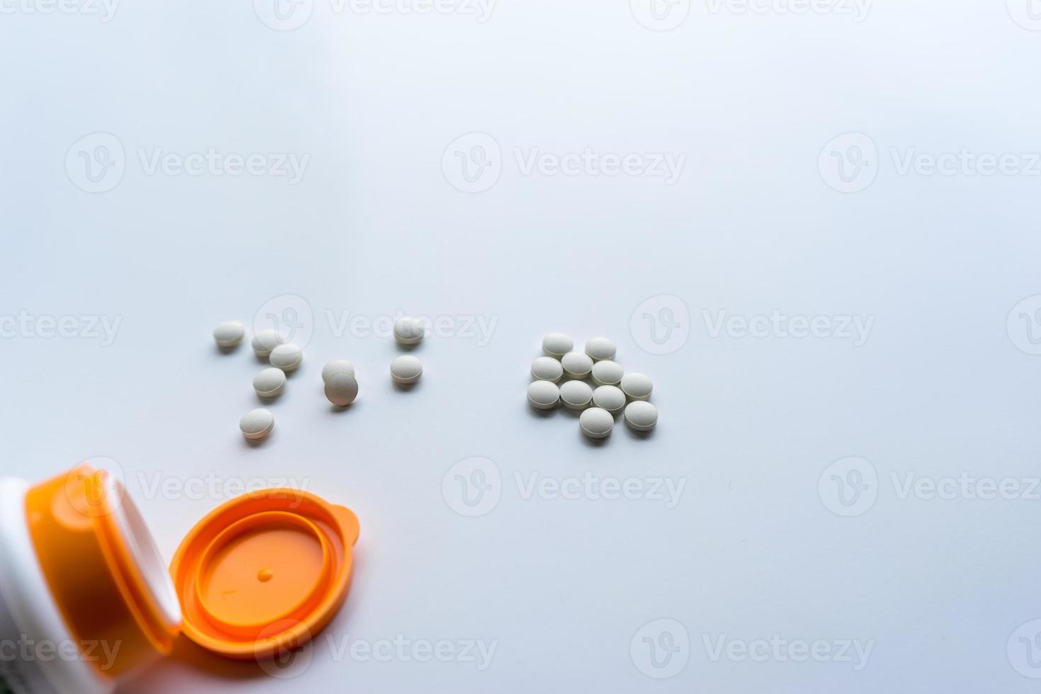 pillole che escono dalla bottiglia di medicina, su sfondo bianco foto