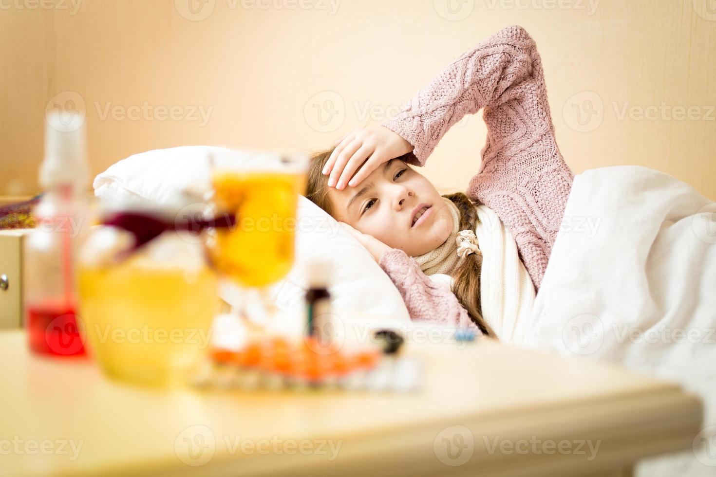 bambina malata con temperatura elevata che si trova nella camera da letto foto
