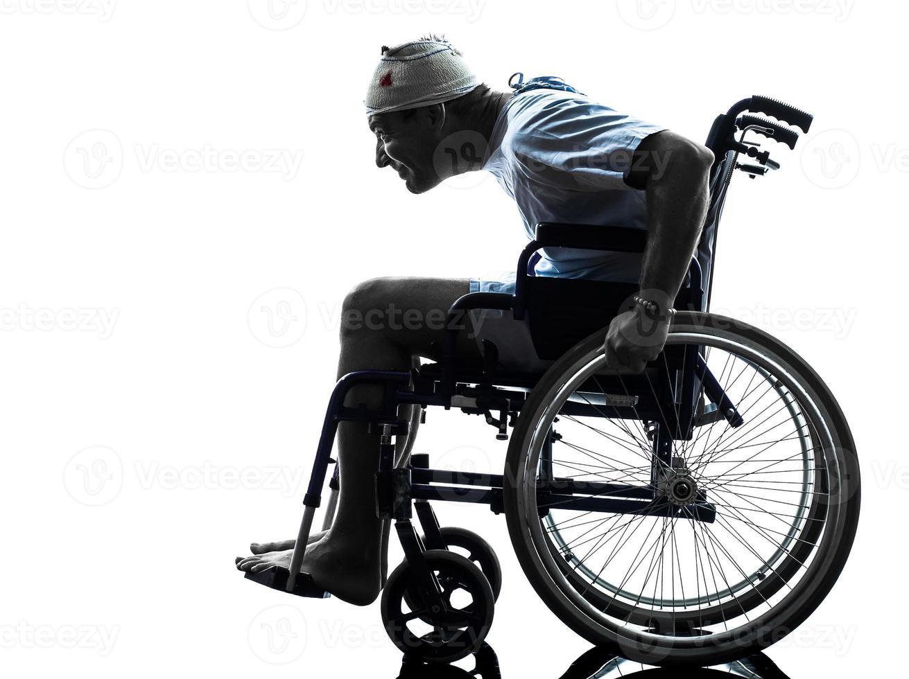 uomo ferito negligente divertente nella siluetta della sedia a rotelle foto