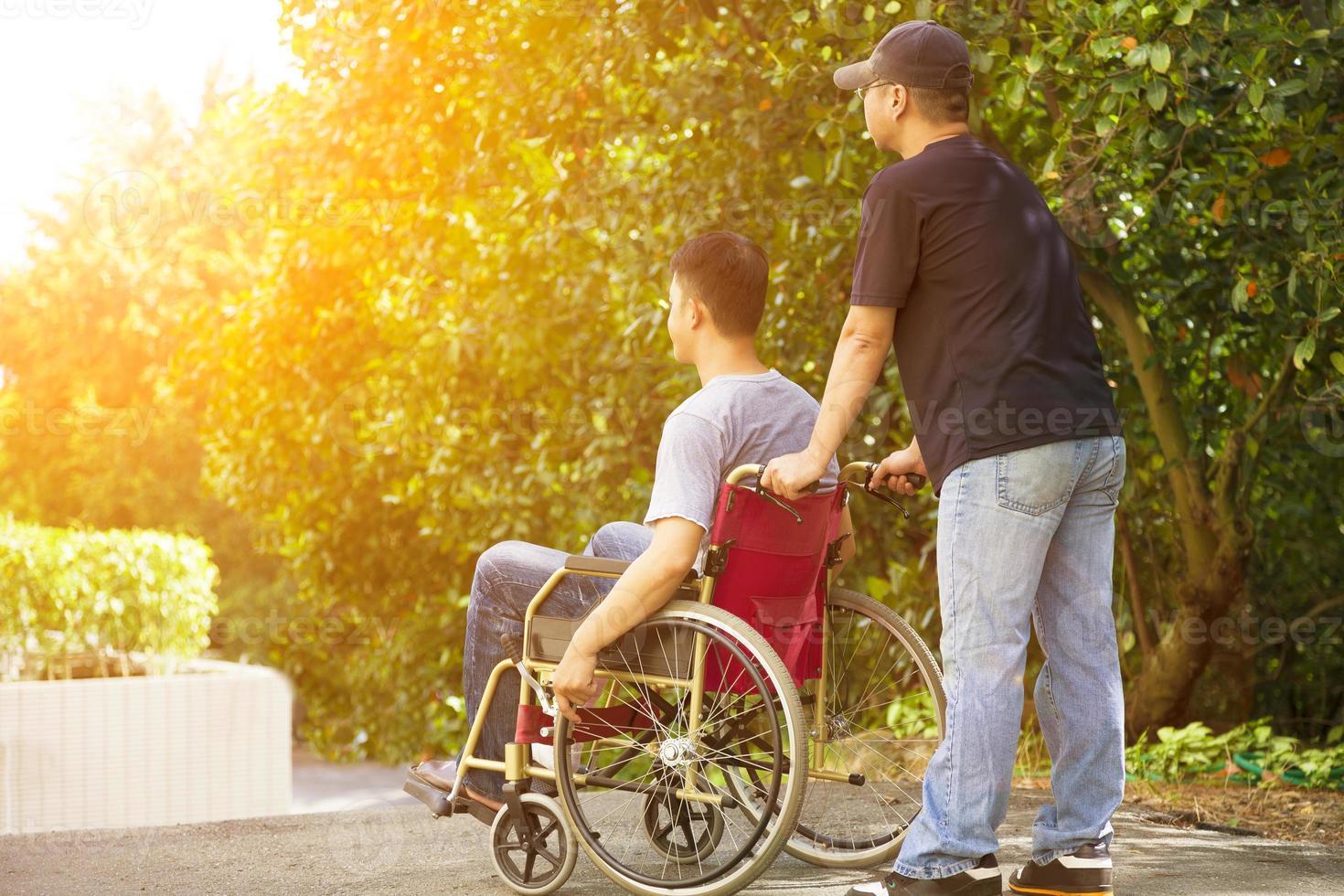 giovane uomo seduto su una sedia a rotelle con suo fratello foto