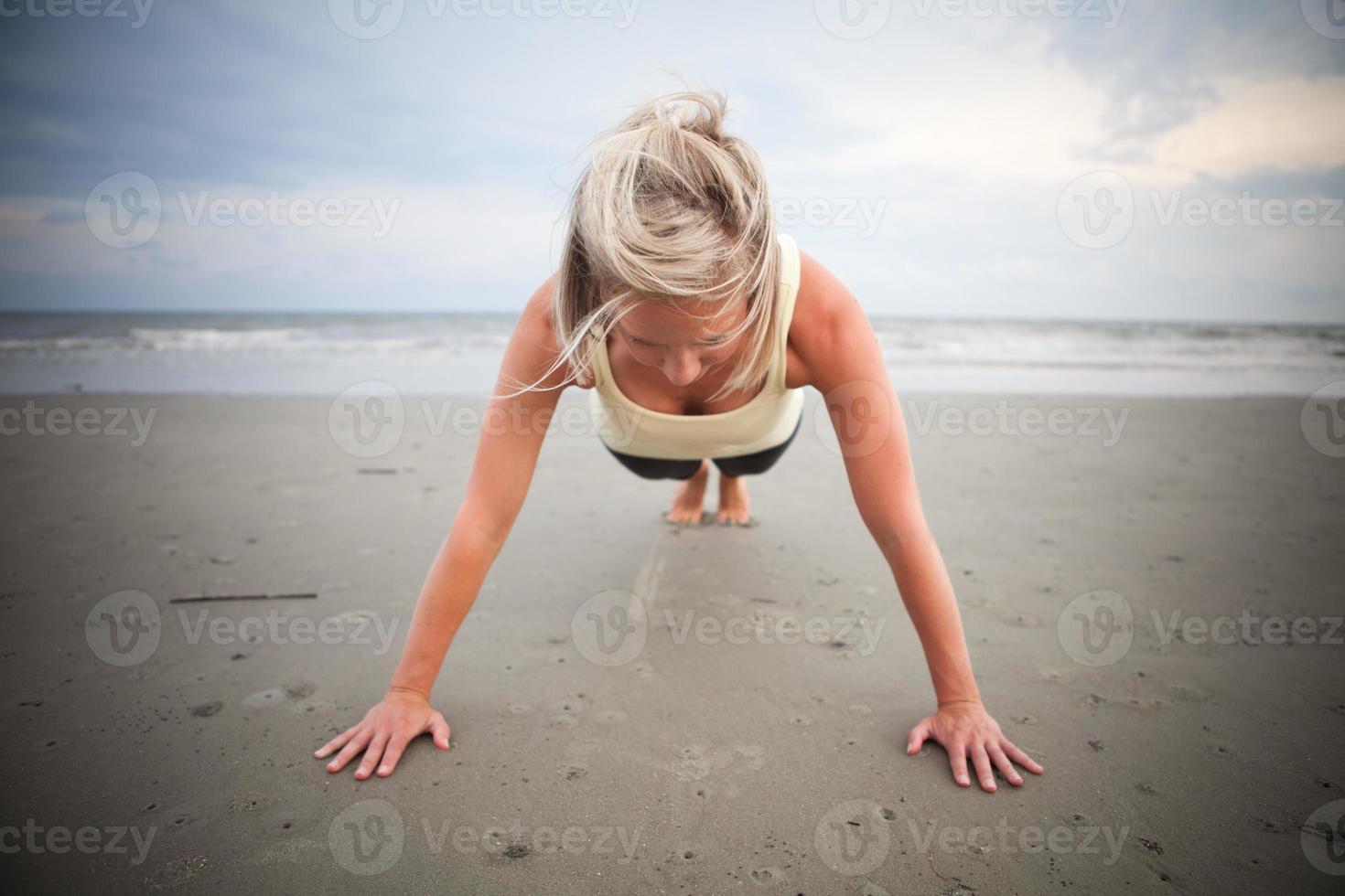 donna che fa push up sulla spiaggia foto