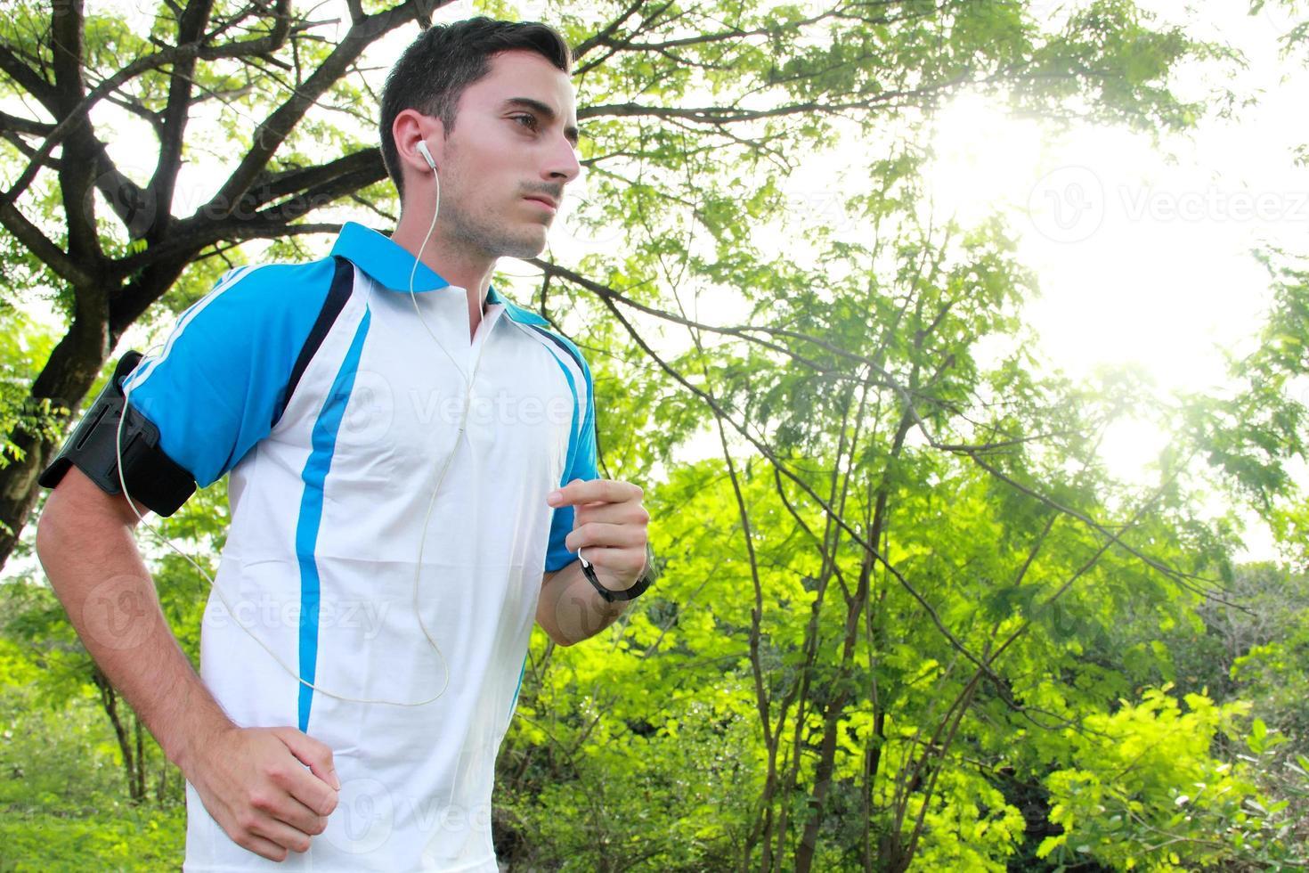 sportivo in forma giovane jogging durante l'ascolto di musica foto