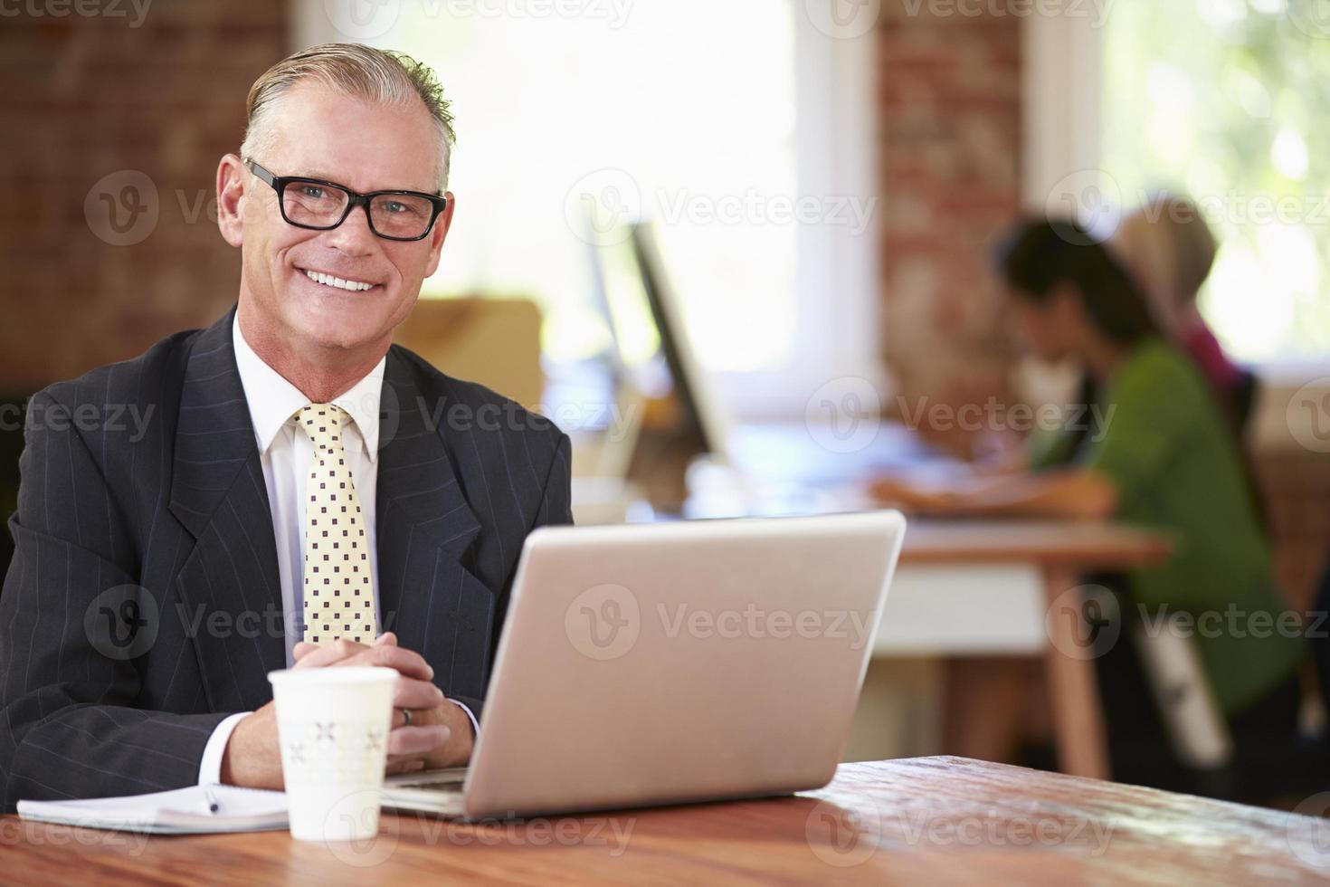 uomo che lavora al computer portatile in ufficio contemporaneo foto