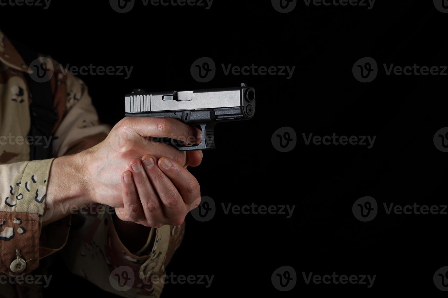 soldato maschio che punta la sua arma nell'oscurità foto