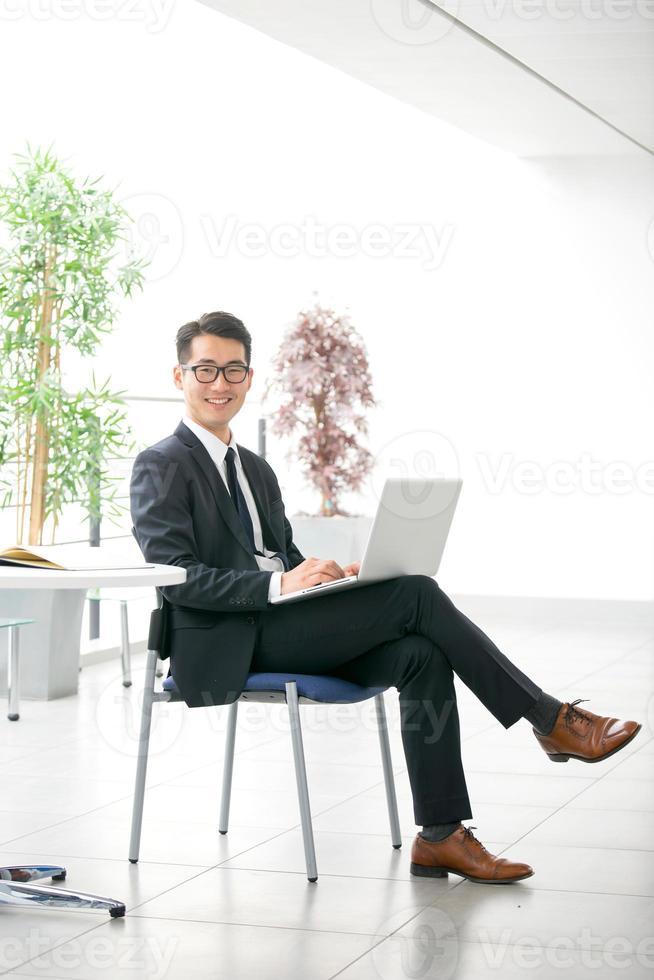 giovane uomo d'affari asiatico facendo uso della compressa, telefono cellulare nell'ufficio foto