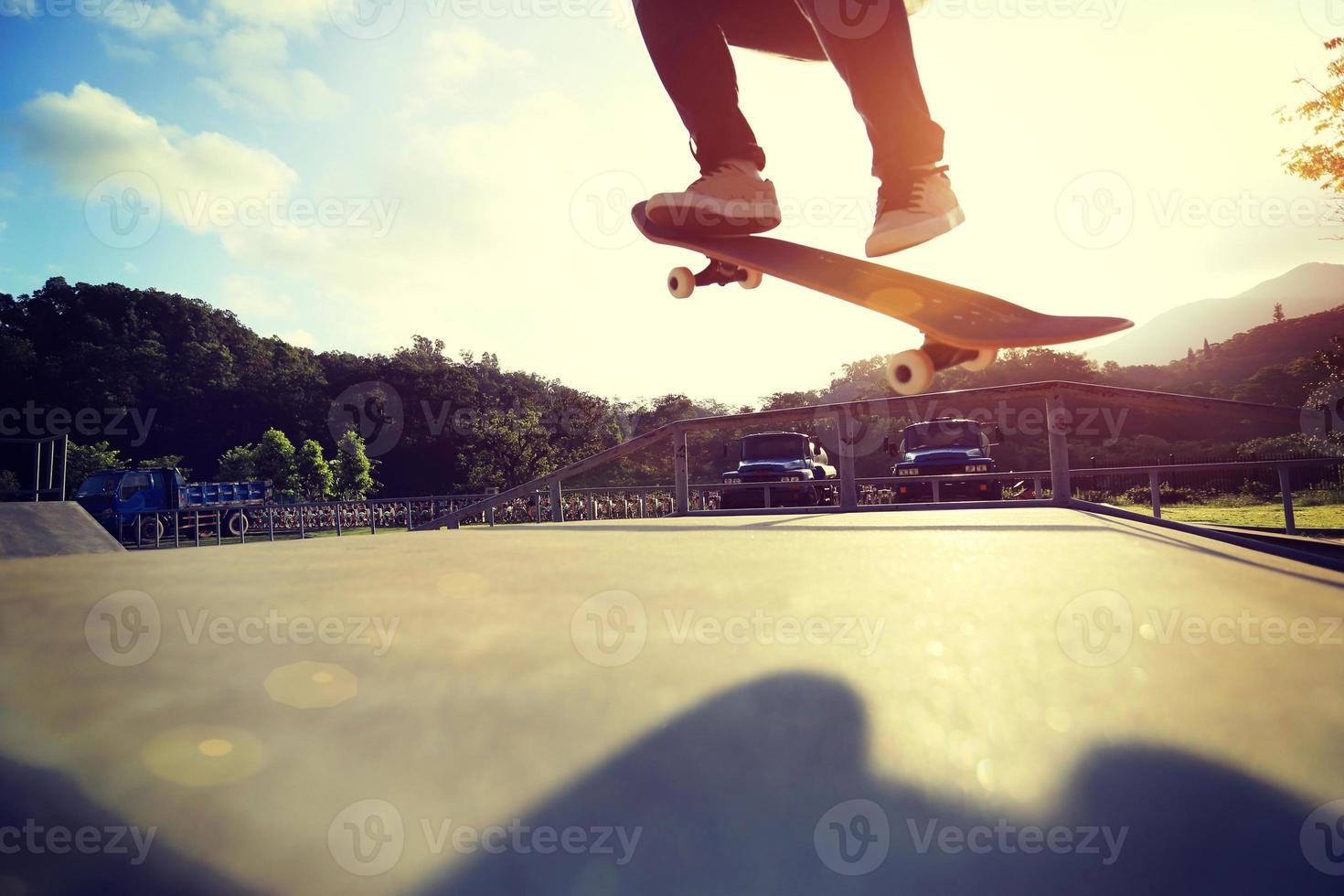 gambe di skateboarder facendo un trucco ollie allo skatepark foto