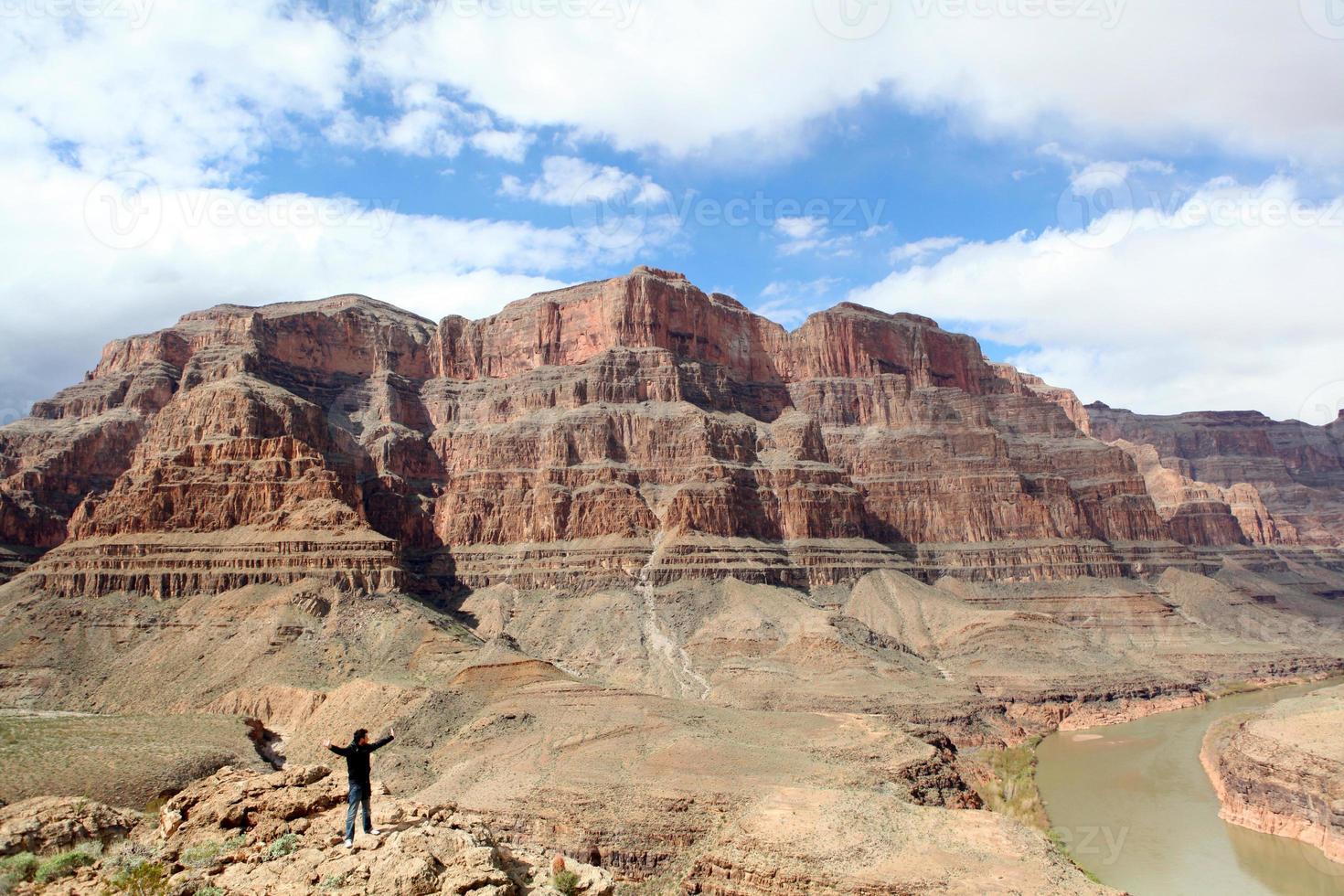 uomo con il braccio alzato sul Grand Canyon foto