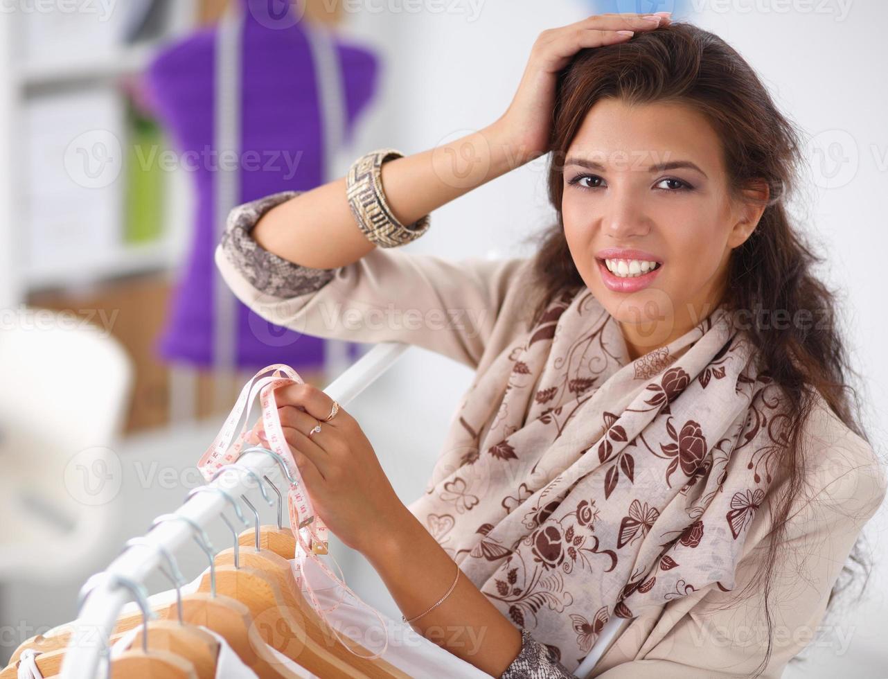 bella giovane donna stilista vicino a cremagliera con appendiabiti foto