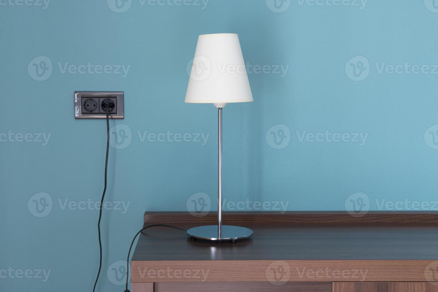 lampada con paralume bianco su un tavolo di legno con sfondo blu foto