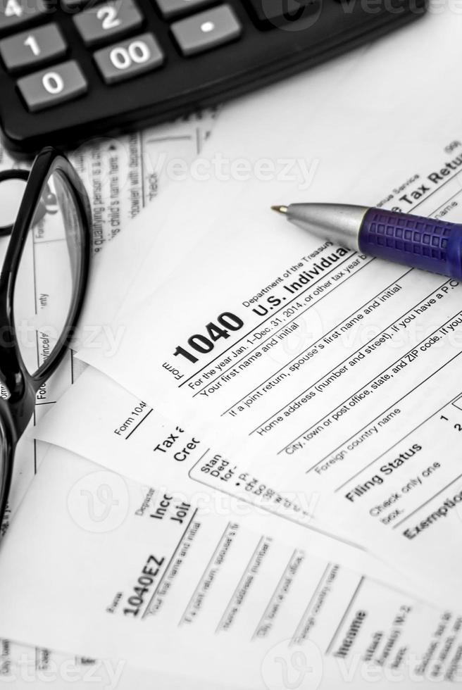 modulo fiscale 1040 con penna, occhiali e calcolatrice foto