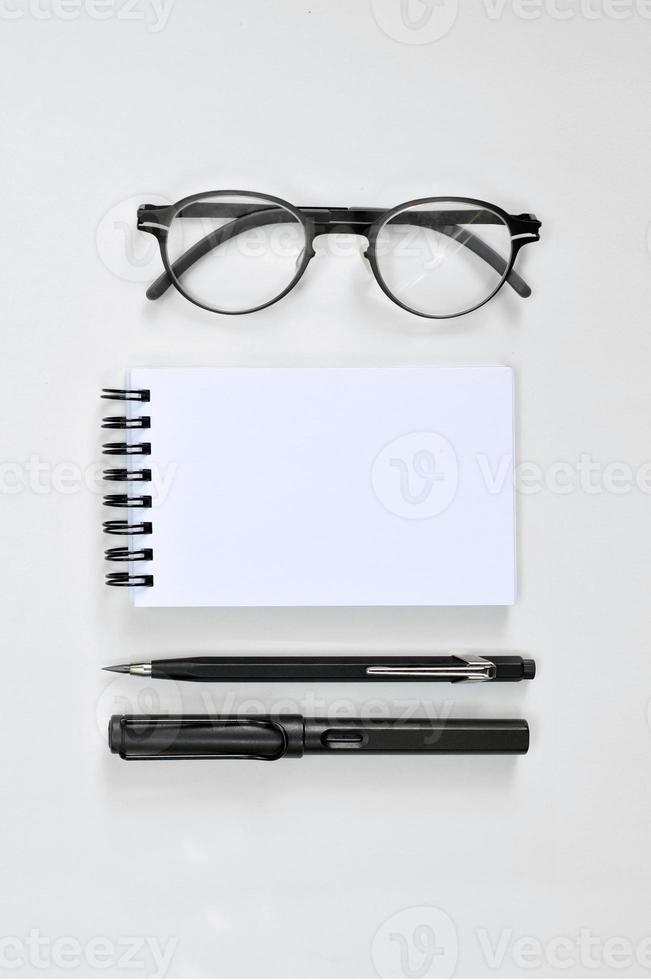 occhiali, blocco note vuoto, penna e matita meccanica foto