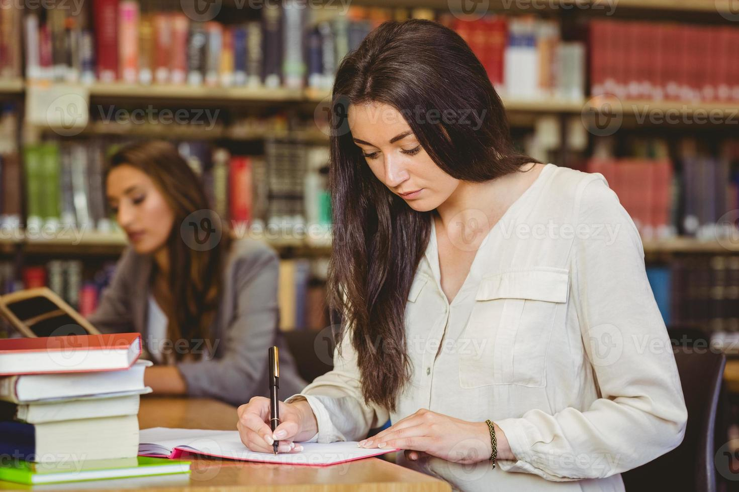 concentrando la scrittura graziosa dello studente in blocco note foto
