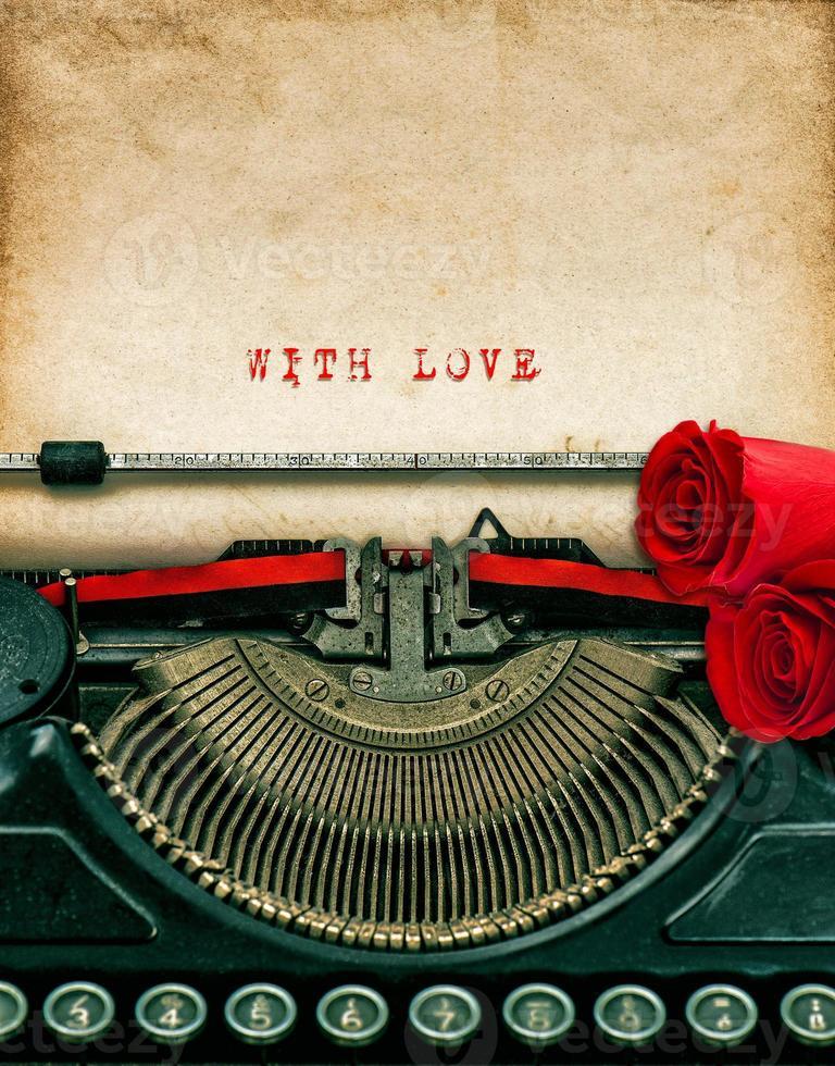 macchina da scrivere vintage e fiori di rose rosse. Con amore foto