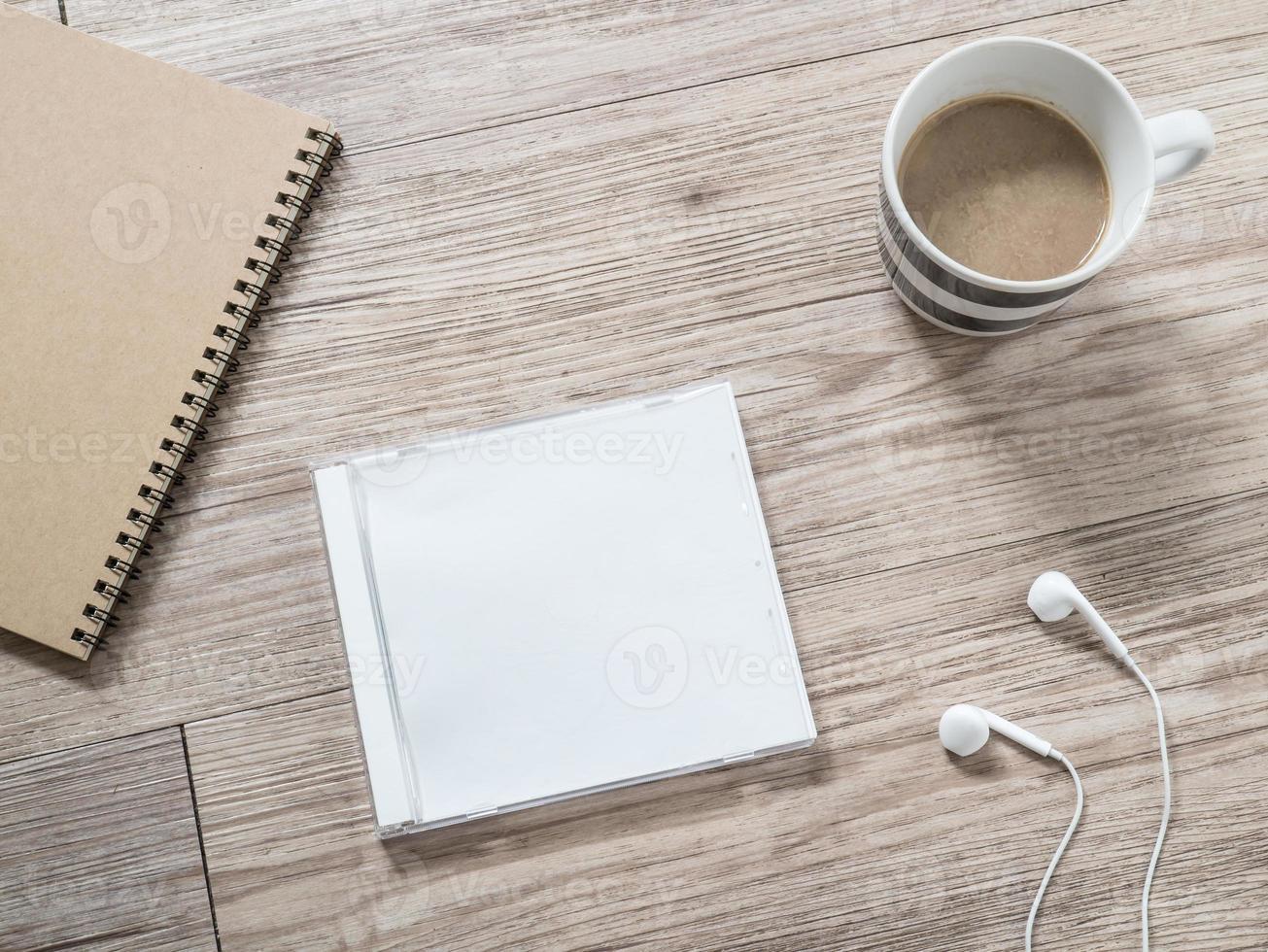 compact disc in bianco, auricolari, taccuino e caffè su fondo di legno foto