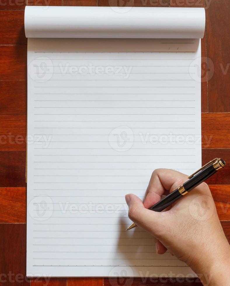la mano scrive sul taccuino con la penna. foto