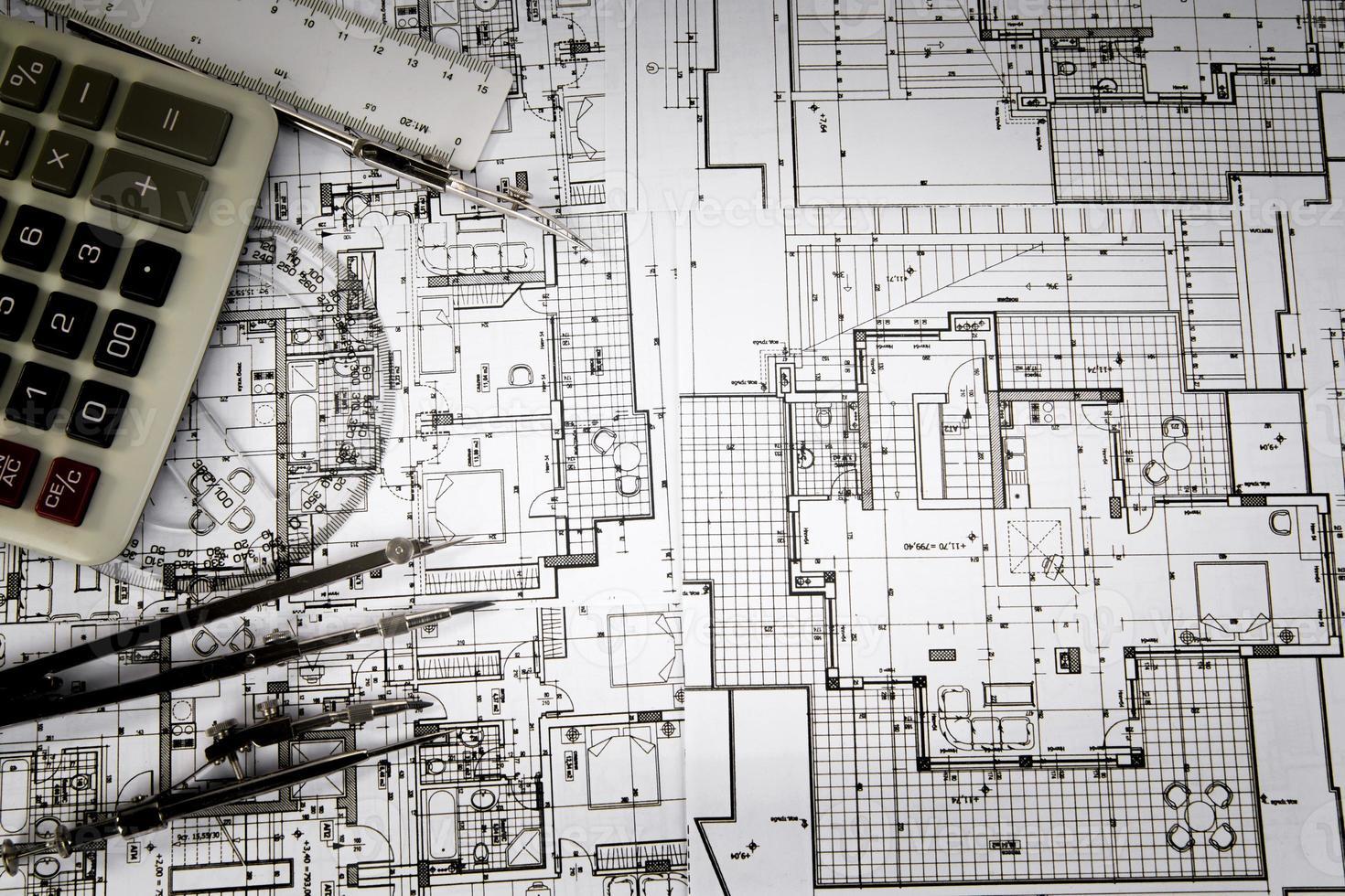 progetto architettonico, coppia di compassi, goniometro e calcolatrice foto