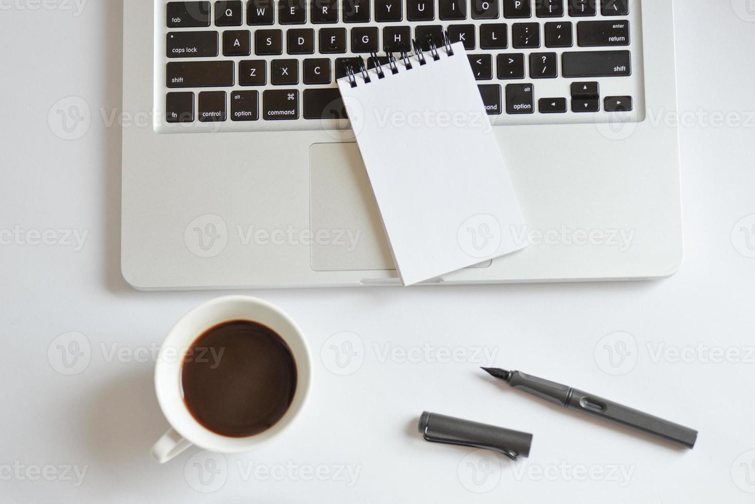 tazza di caffè, blocco note a spirale, tastiera del computer e penna su bianco foto