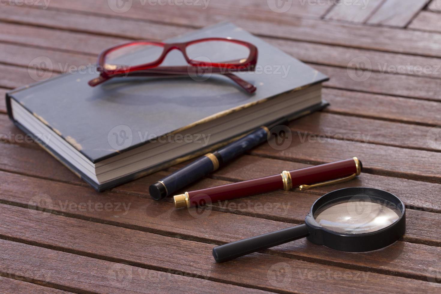 libro chiuso, occhiali rossi, stilografica e penna a sfera foto
