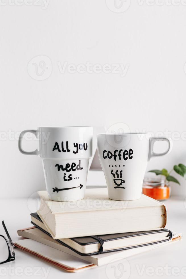 due tazze di caffè con scritta su una pila di libri foto