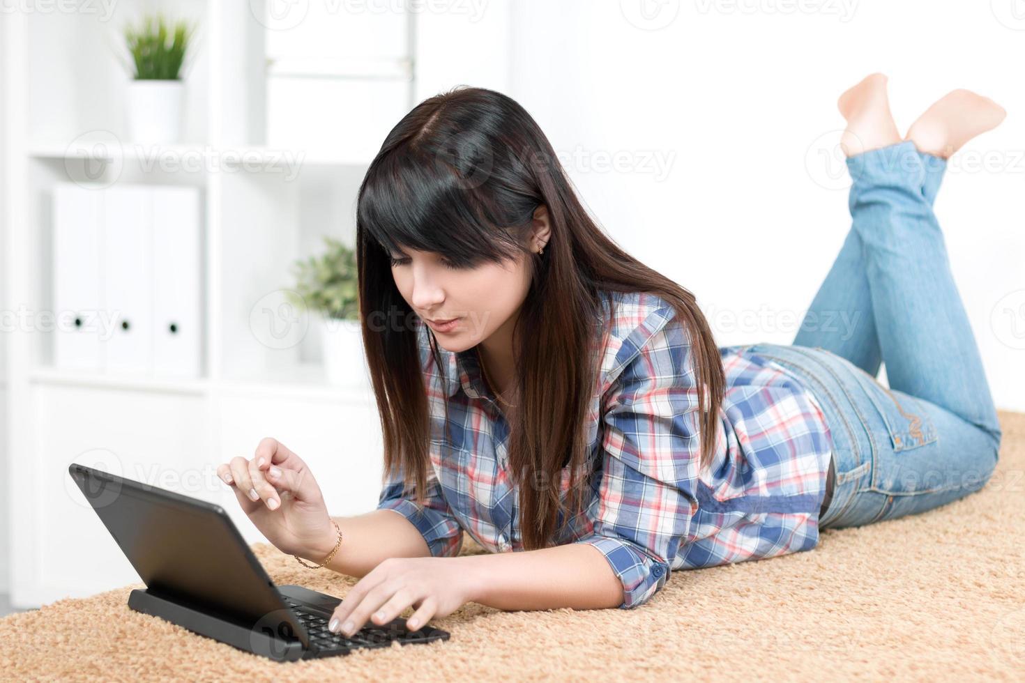 ragazza dell'adolescente che studia a casa sdraiato sul divano foto