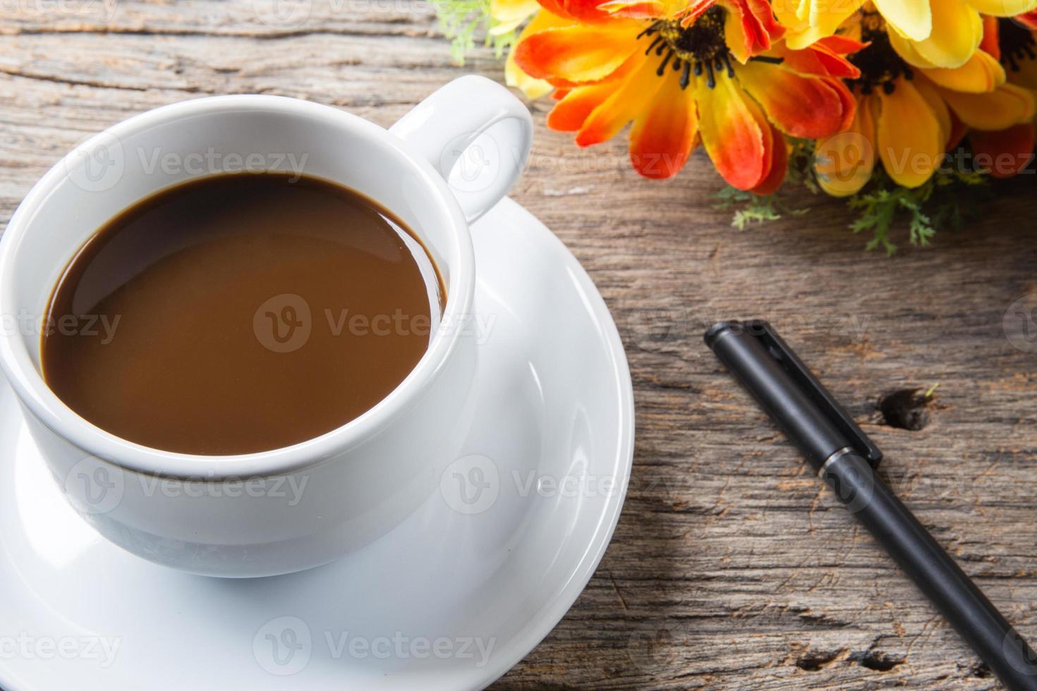 tazza di caffè, penna sul tavolo di legno foto