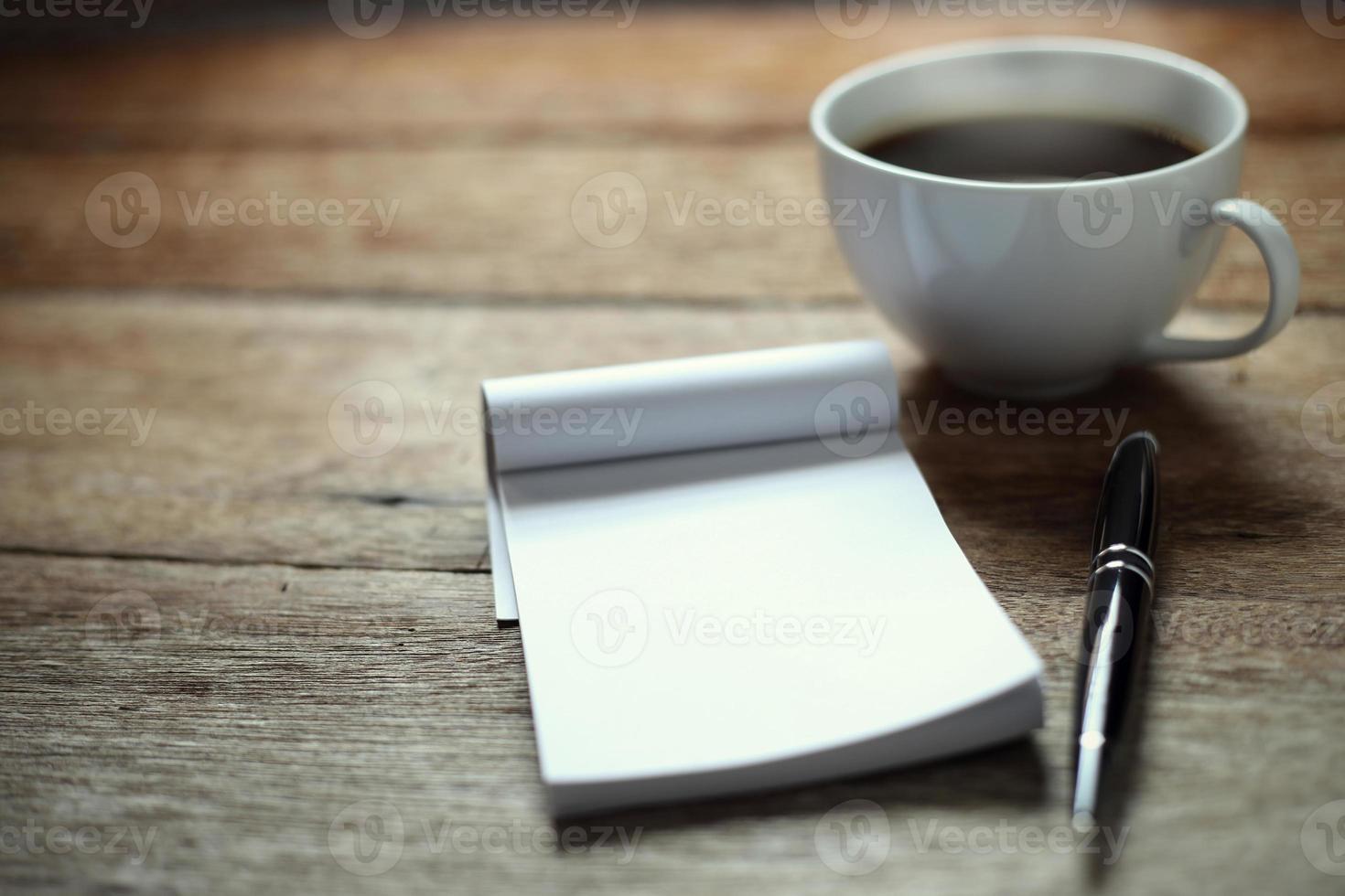 aprire un quaderno bianco vuoto, una penna e una tazza di caffè foto