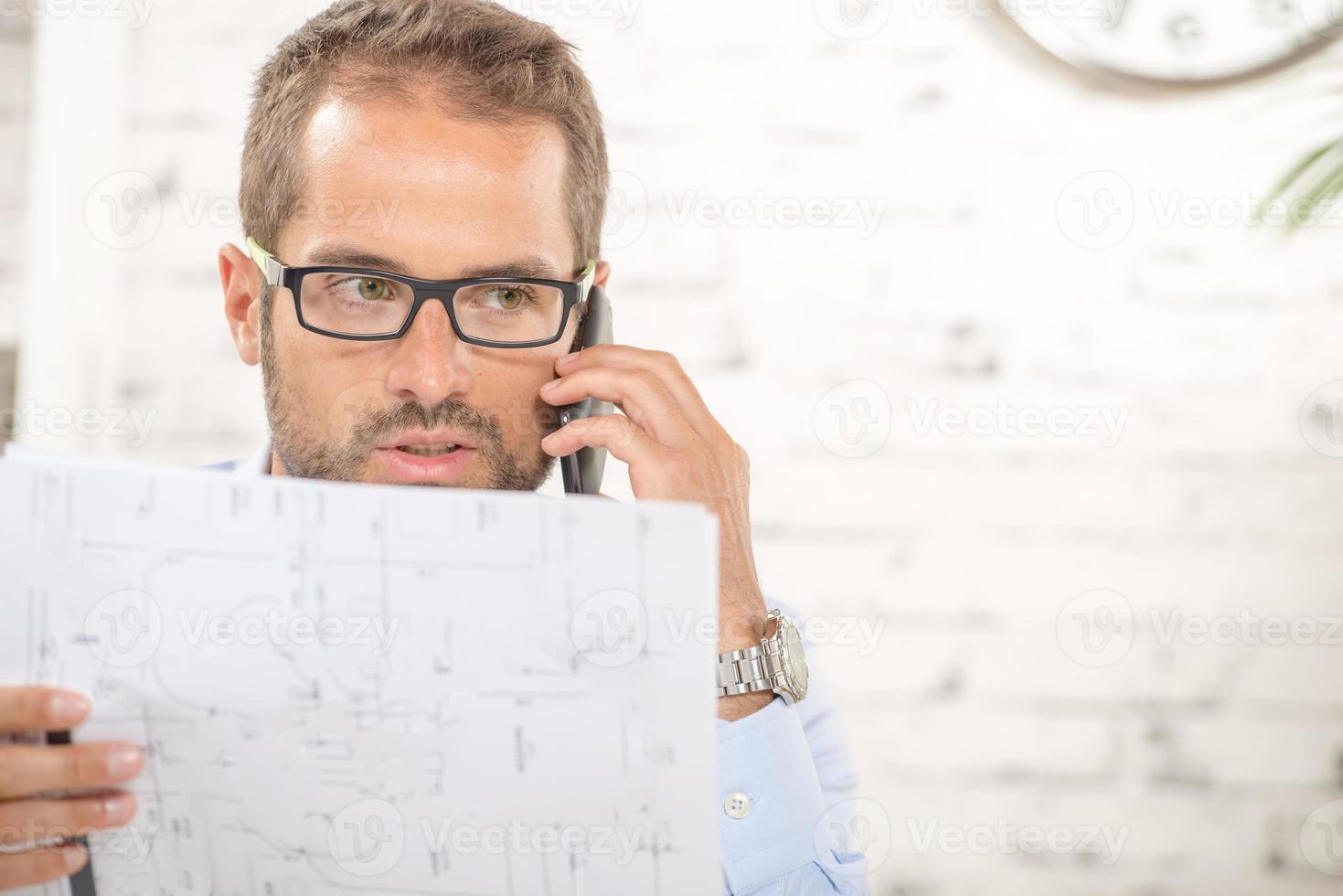 giovane con gli occhiali legge un piano e un telefono foto