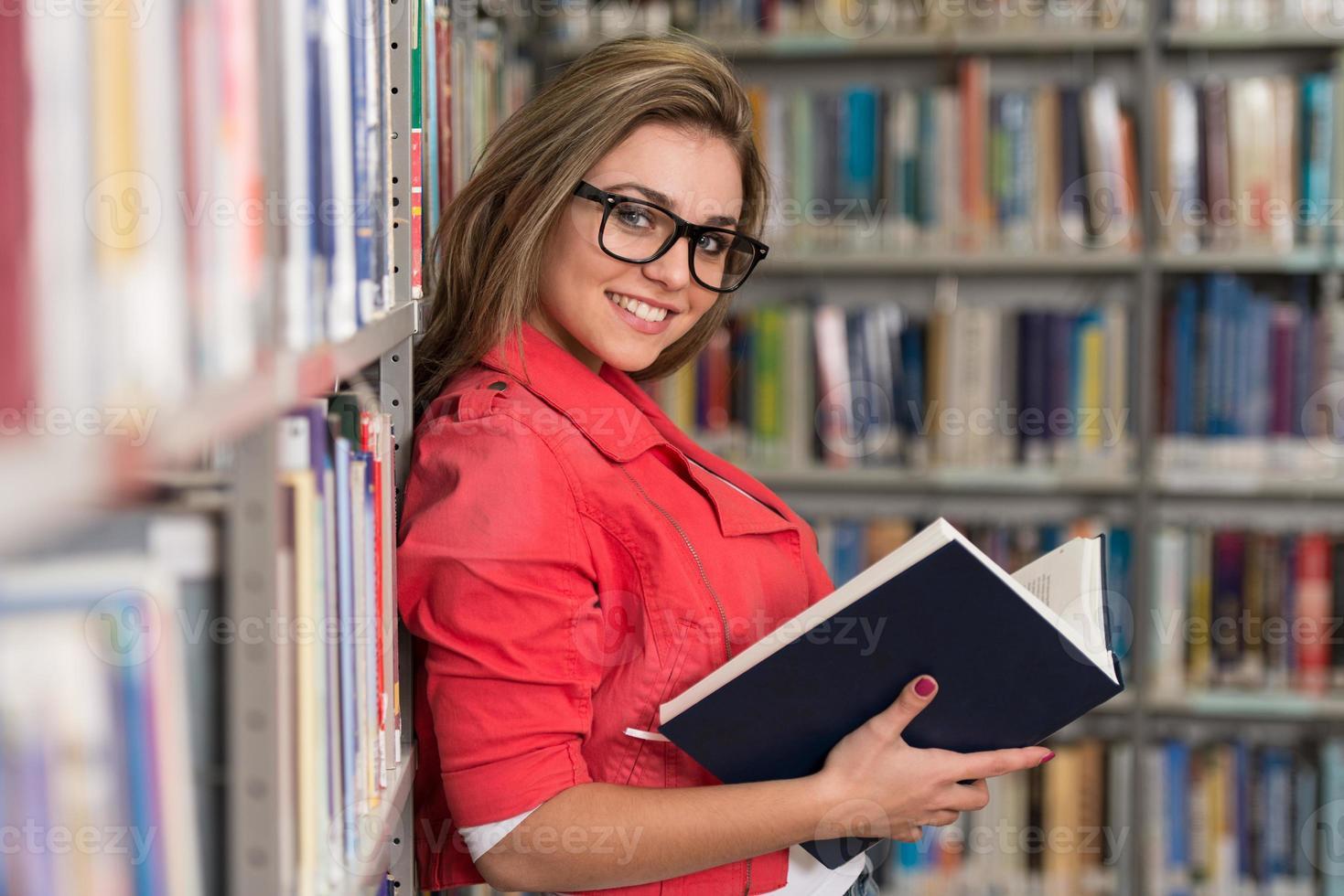 Ritratto di una ragazza studentessa che studia in biblioteca foto