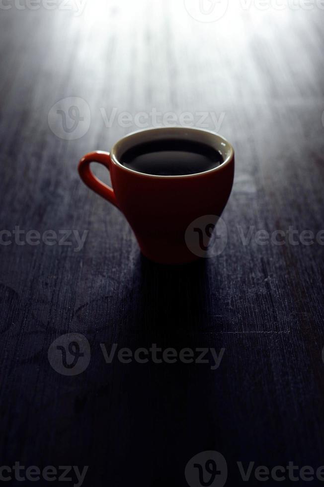 tazza arancione con caffè sul tavolo, immagine scura foto