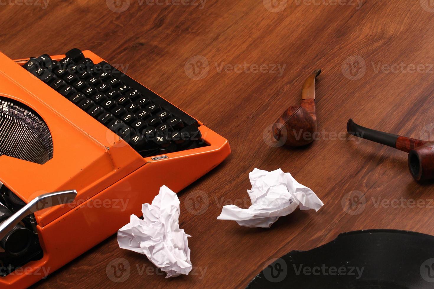 la macchina da scrivere vintage arancione sul legno foto